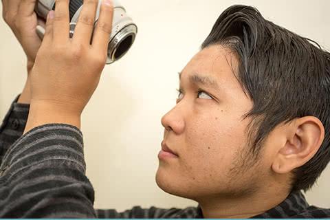 イメージ写真 買取屋さんの男性査定スタッフがカメラを査定しているイメージ写真