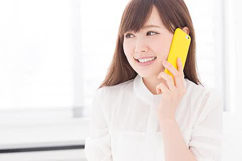 イメージ写真 長髪の女性が笑顔で買取屋さんへ電話する様子のイメージ写真