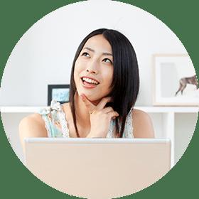 イメージ写真 パソコンを前に笑顔で考える黒髪の女性のイメージ写真
